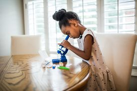 young girl looking in toy microscope