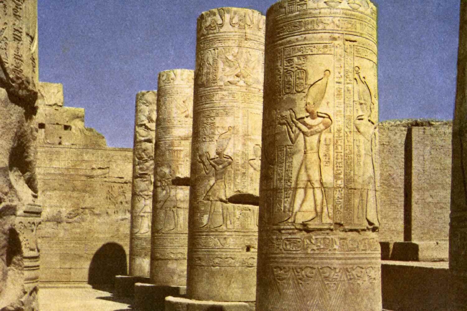 parts of large columns ornately carved with Egyptian figures and designs