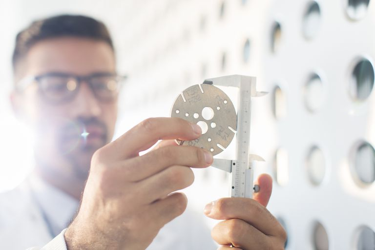Scientist using calipers to measure a disc