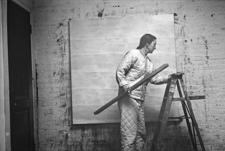 Agnes Martin stands in an art studio with level and ladder