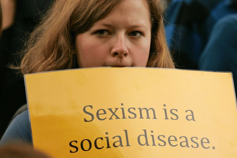 Woman holding a sign that says sexism is a social disease
