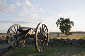 Cannon facing the horizon over a low stone wall