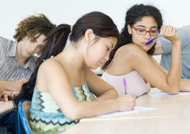 Students taking test in class, one student looking at another's paper