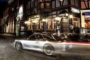 Porsche 911 speeding down the street in a German town at night