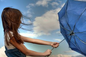 Young girl holding an umbrella that is inside out
