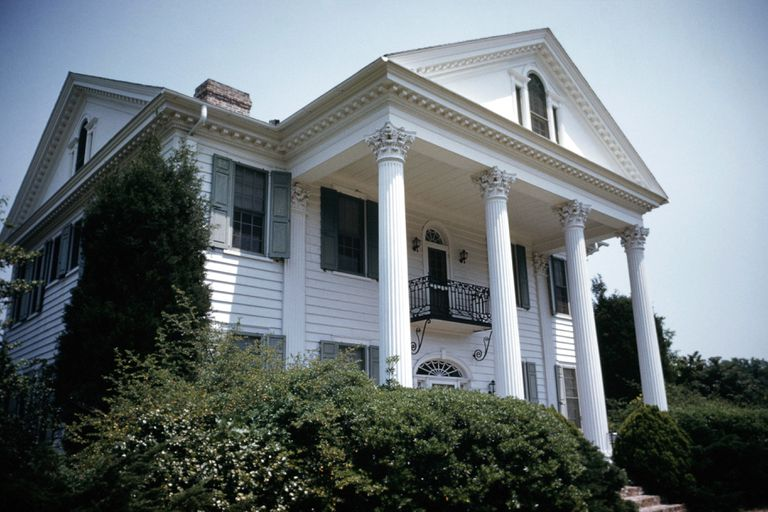 The portico of an classic antebellum plantation home, with lines of tooth-like dentils in the pediment and the cornice