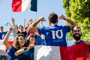 French people waving flags and smiling on a sunny day.