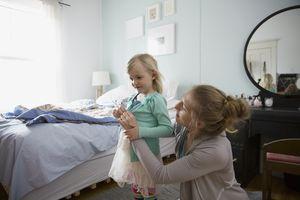 Mother dressing daughter in bedroom