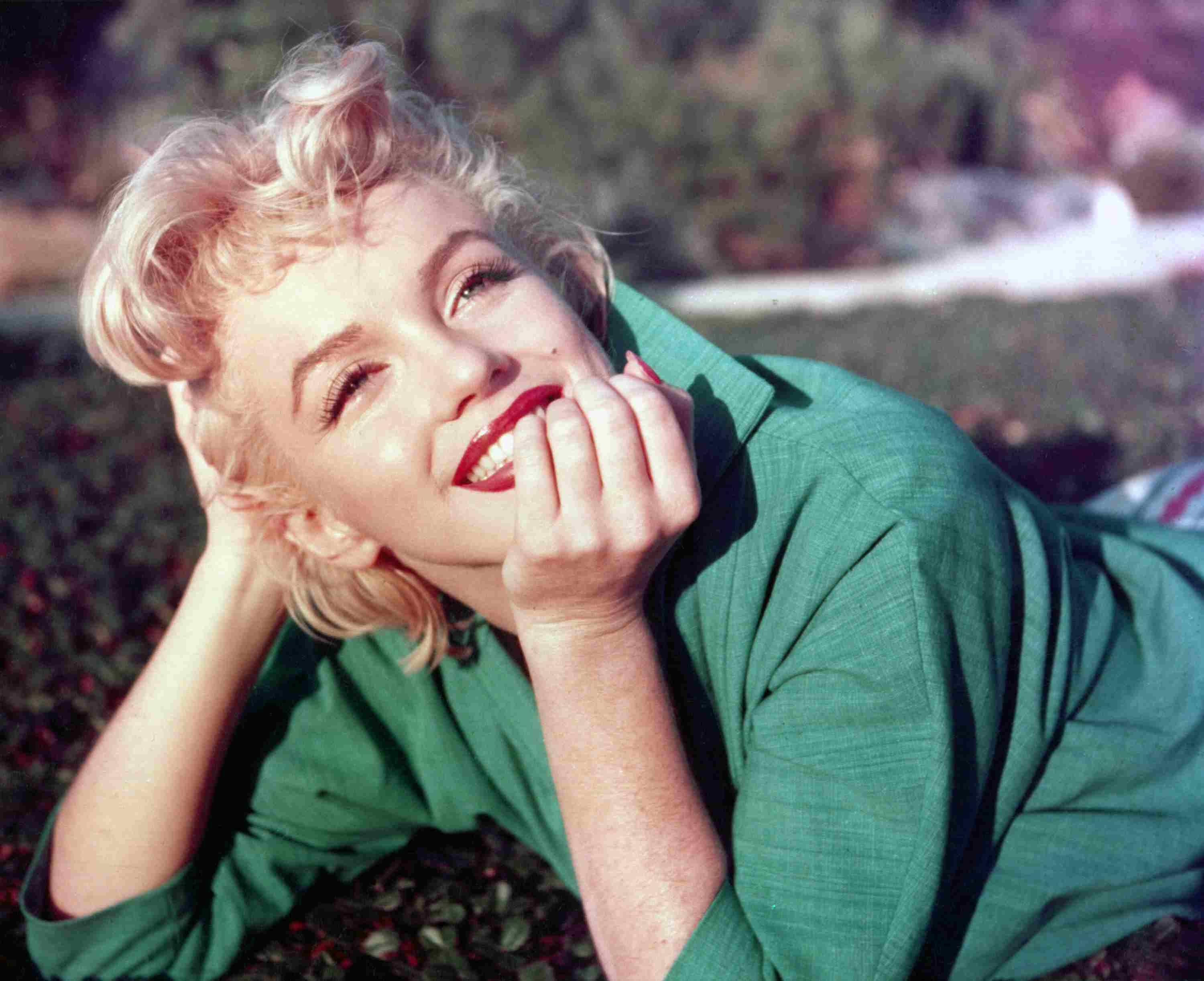 Actress Marilyn Monroe poses for a portrait laying on the grass