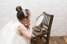 Little girl looking at the mirror