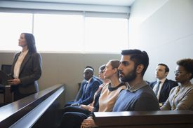 Serious, attentive jury listening in legal trial courtroom