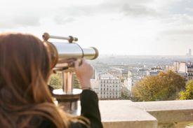 Woman looking at Paris through telescope