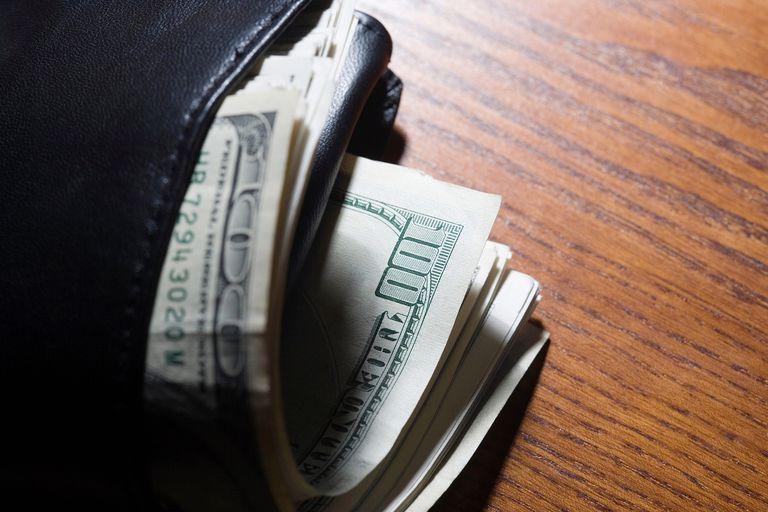 Fajo de billetes de dólar americano saliendo de una cartera