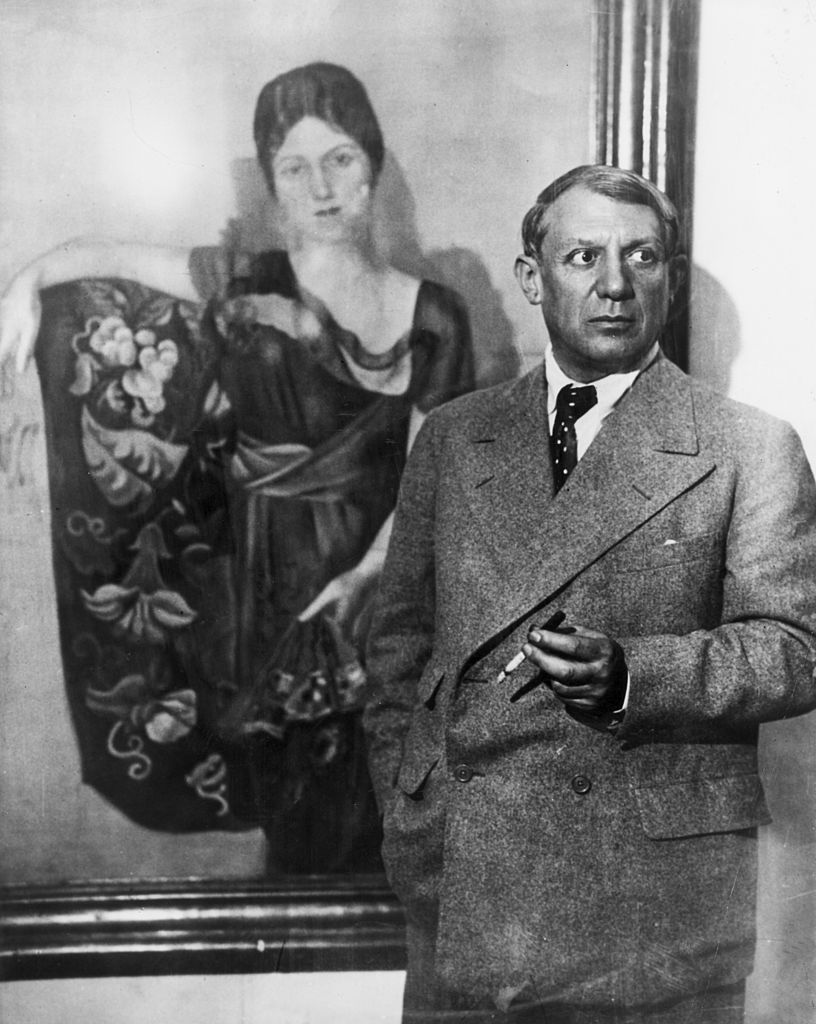 Pablo Picasso standing in front of painting of his wife Olga