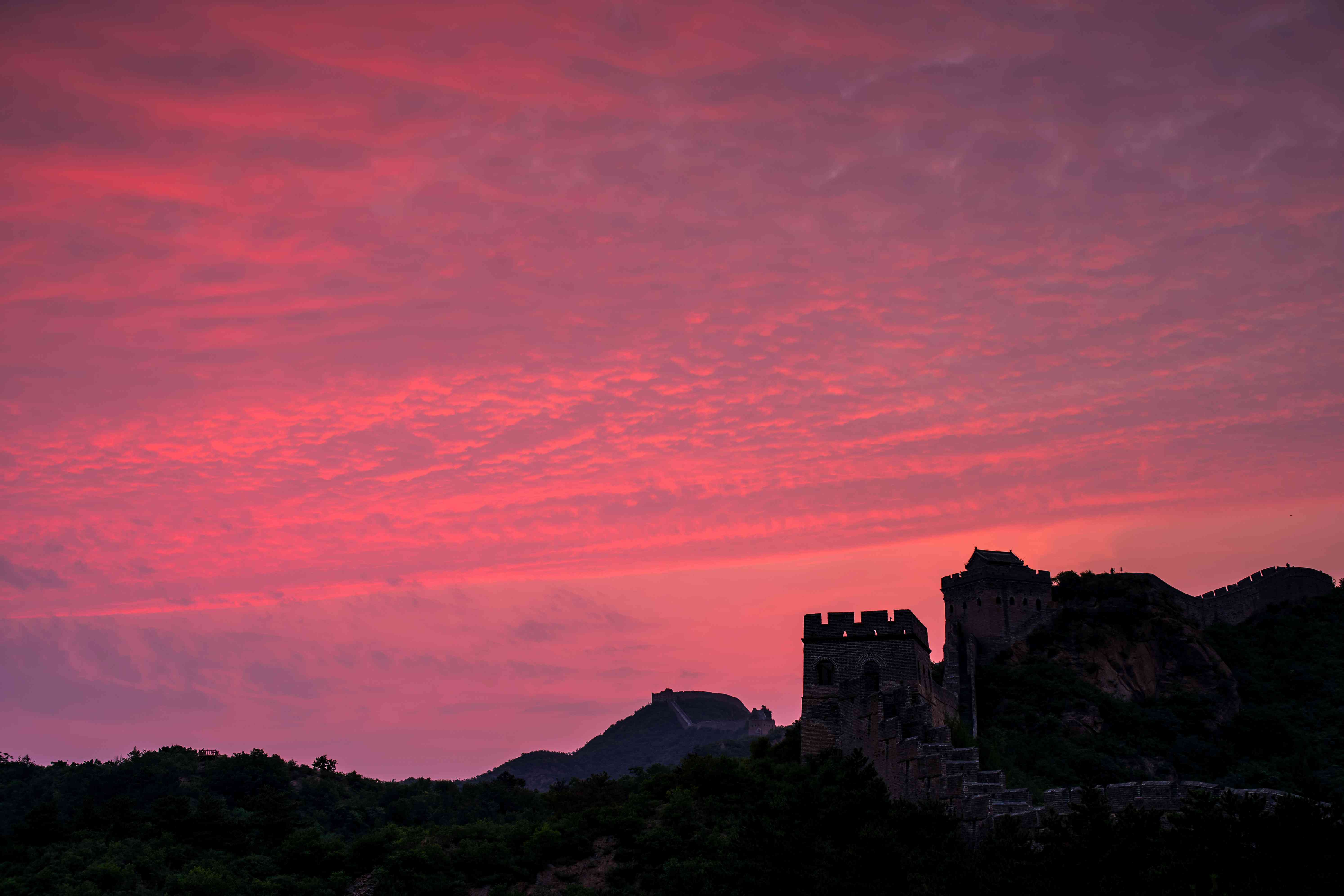 The Jinshanling Great Wall, built in 1368 and located in Chengde City, Hebei, is bathed in the light of a pink sunset