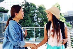 Smiling Friends Shaking Hands While Standing Outdoors