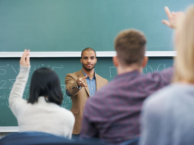 a teacher in front of a classroom of students with hands raised