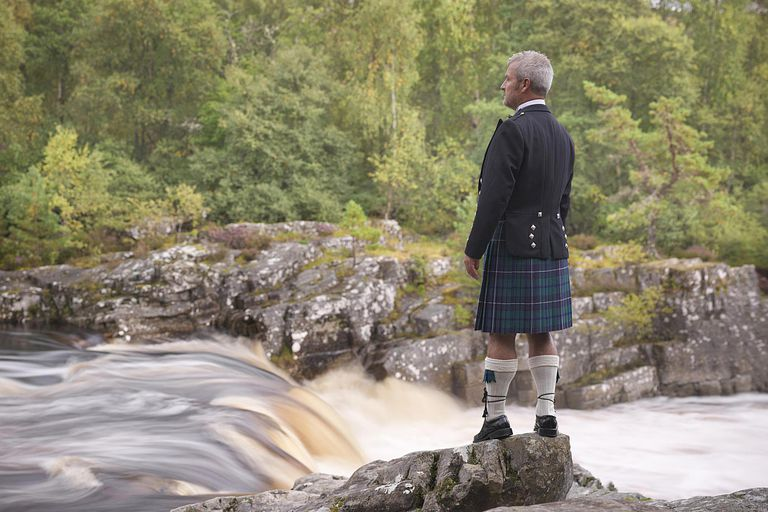 Man in kilt by river