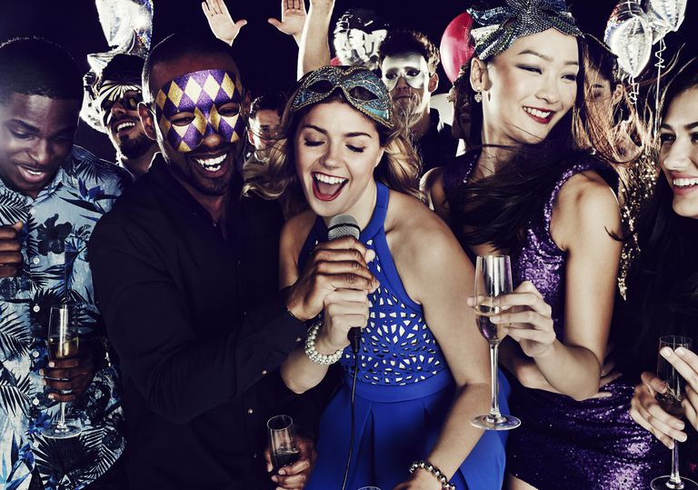 young people holding champagne flutes and celebrating with Mardi Gras masks