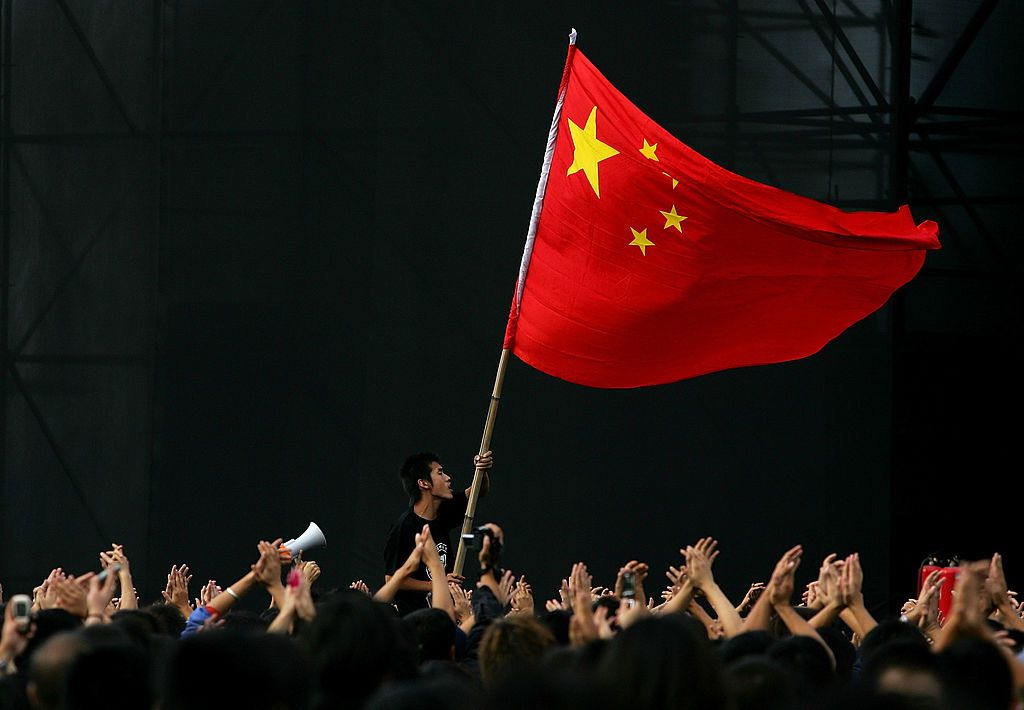 A Chinese teenager waves a national flag during a festival to mark Chinese National Day in Beijing, China.
