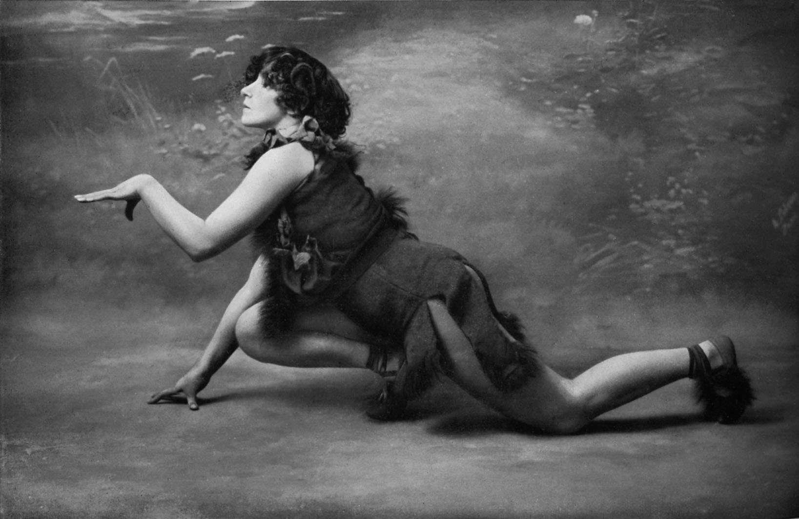 Colette medio arrodillada en el escenario con un traje sin mangas y una falda rajada