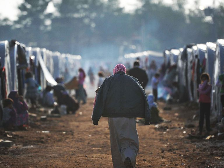 person walking through refugee camp