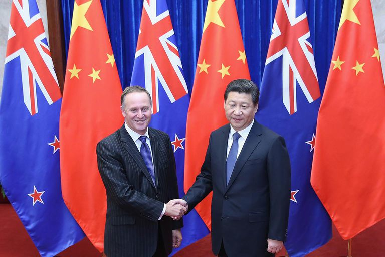 Two men dressed in suits shaking hands in front of flags