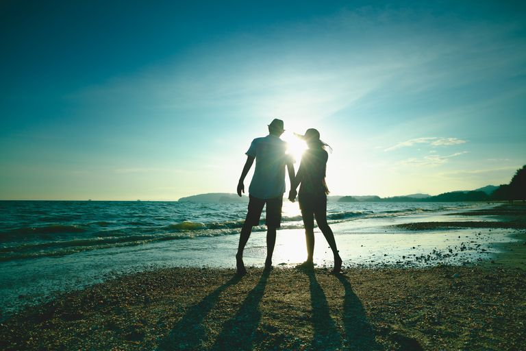 couple holding hands on the beach during summer