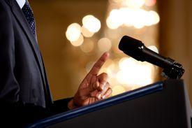 Obama at podium holding one finger up