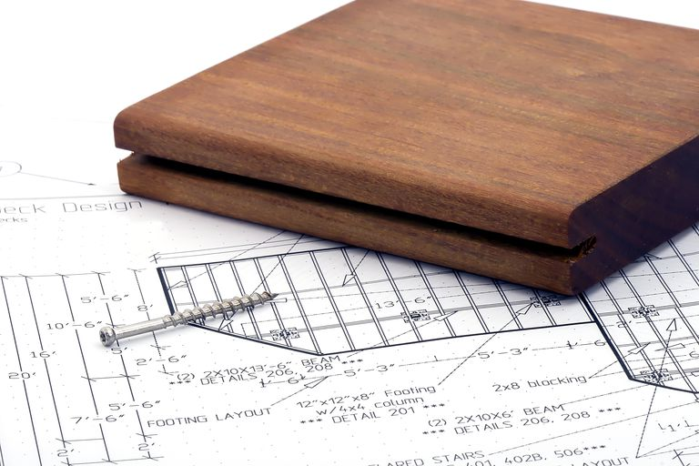 sample of grooved wood and a wood screw on top of deck design drawings