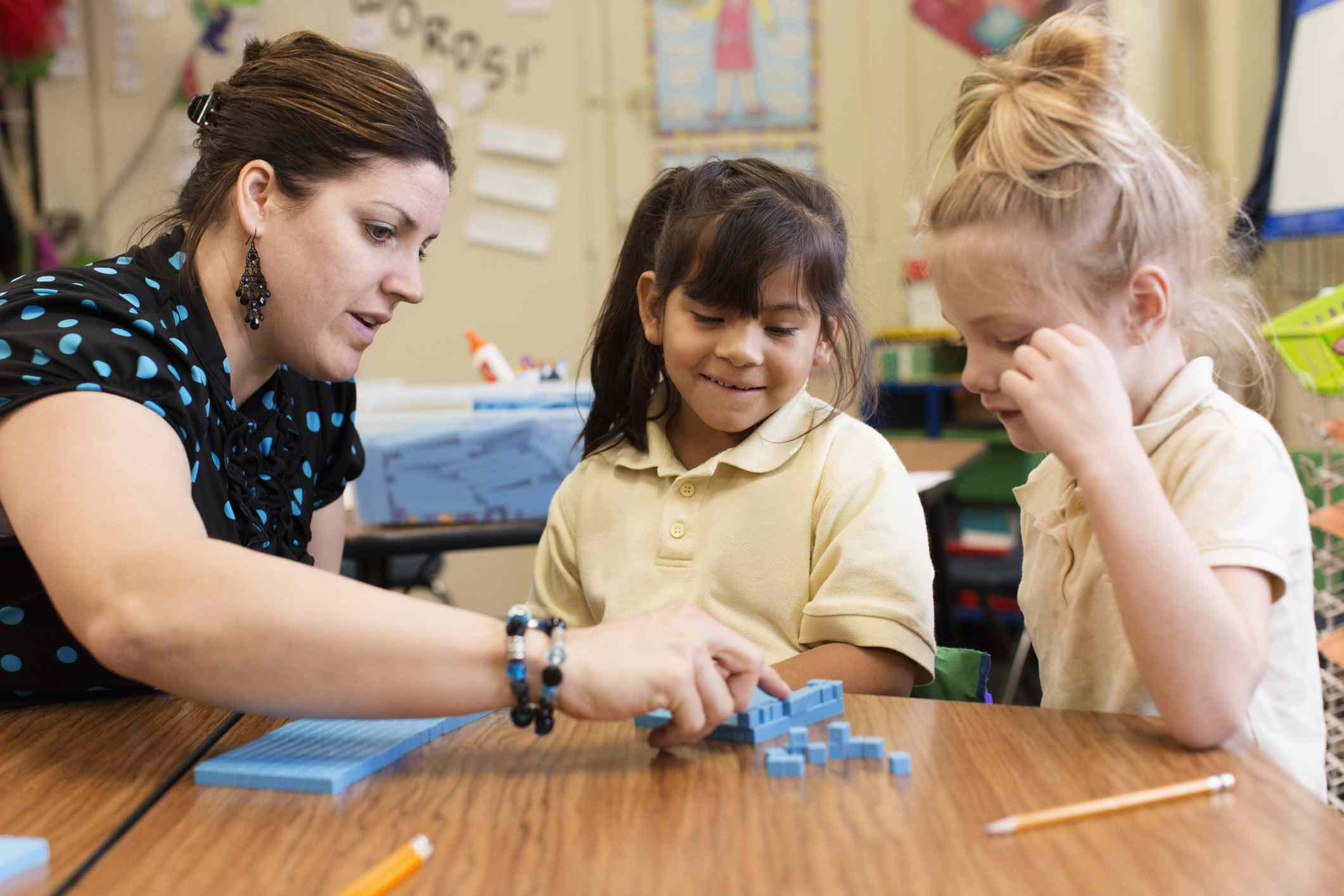 teacher working with students with blue cubes