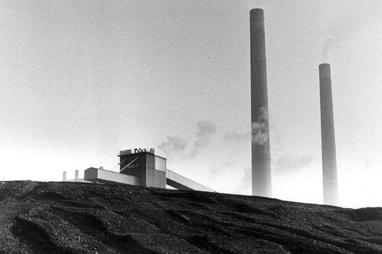 A Coal Mountain Site with smokestakes in the background