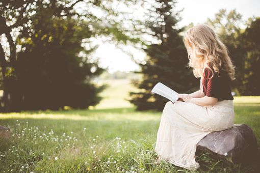 Woman sitting on a rock in a field, reading the Bible.