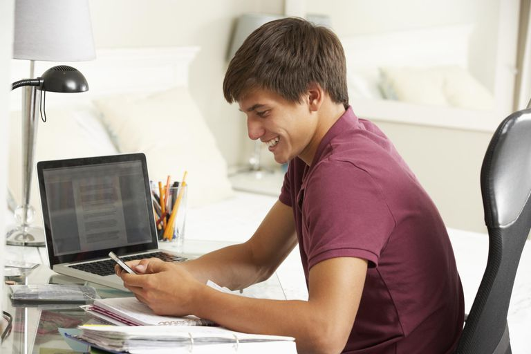 Teenage Boy Studying At Desk In Bedroom Us...