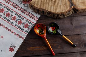 wooden Russian hand-painted spoons and tablecloth with a traditional pattern on natural wooden background. Top view.