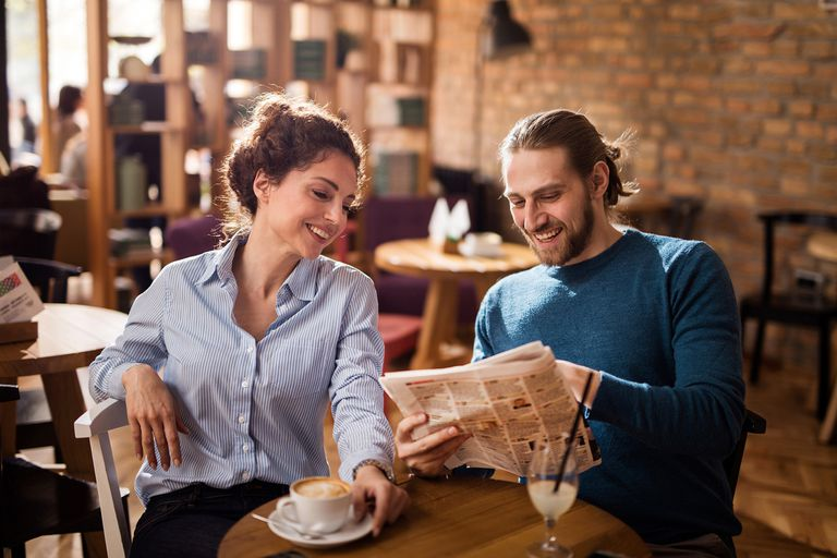 couple reading newspaper in coffee shop