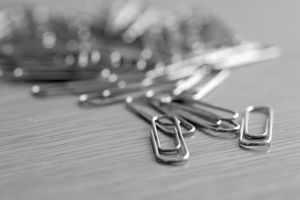 Close up of a pile of paperclips on a gray surface.