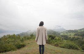 Woman standing in a mountain looking to the view