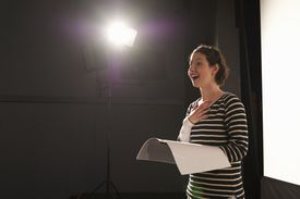 Actress rehearsing under spotlight on stage.