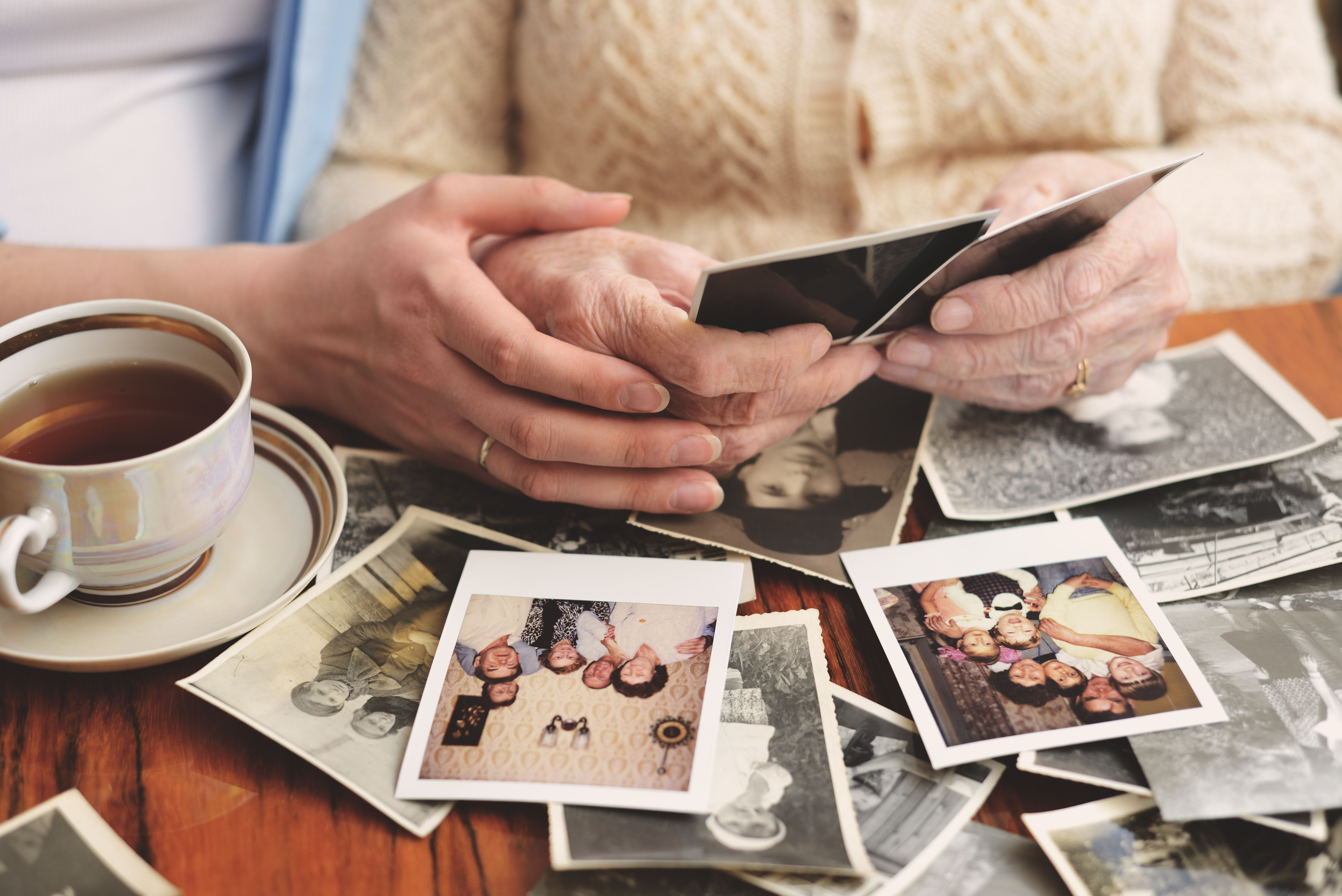 Senior woman and granddaughter sitting at table, looking through old photographs, mid section