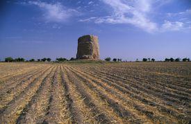 A Buddhist stupa rises over a field in Uzbekistan