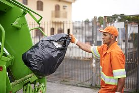 A garbage collector deposits a trash bag into a truck