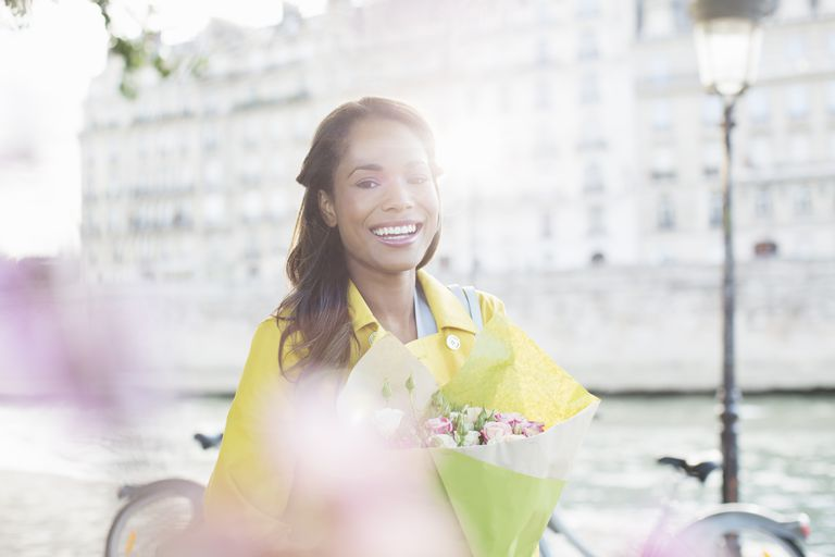 Woman with bouquet of flowers along Seine River, Paris, France