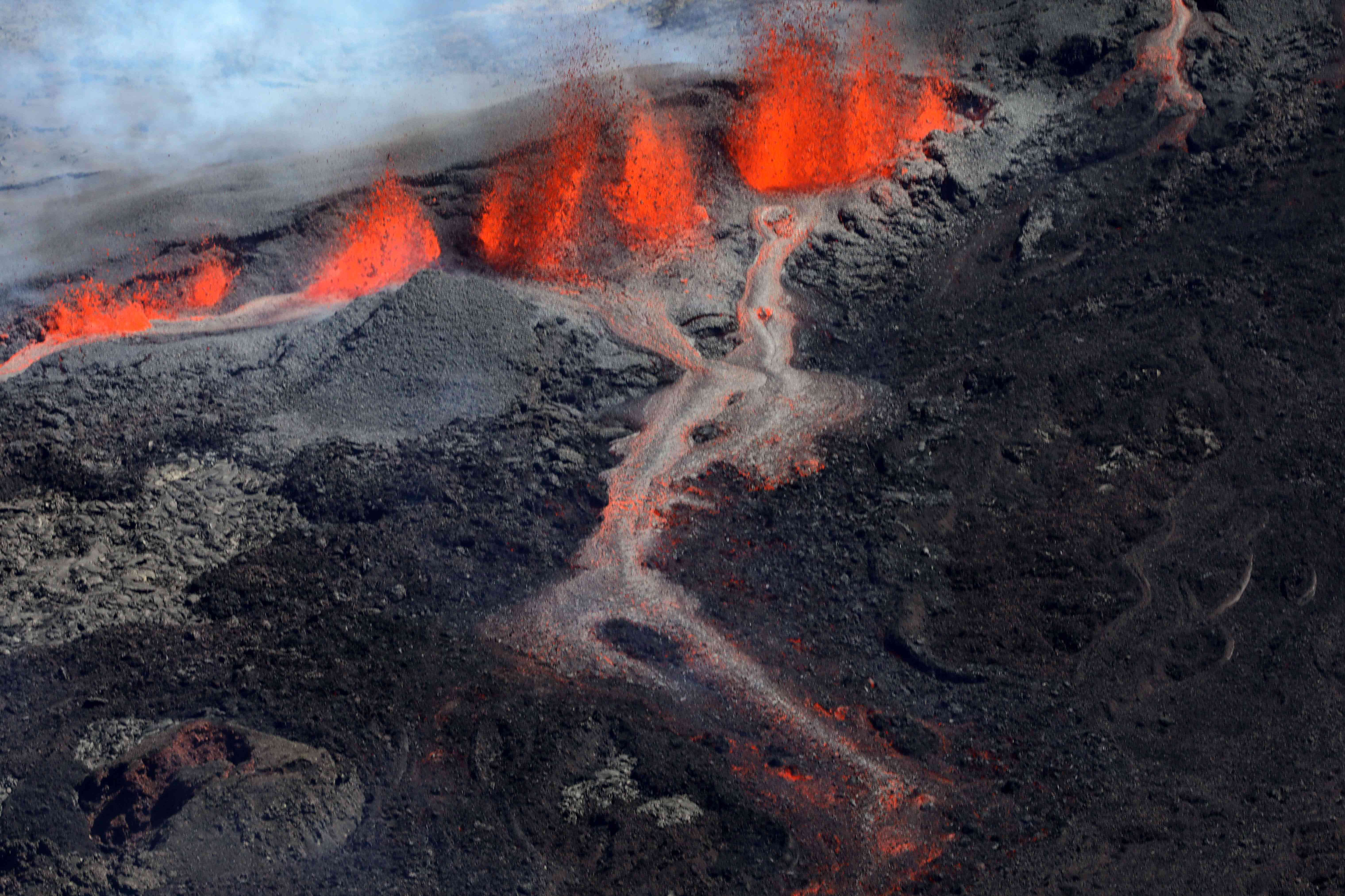 Lava erupts from the Rivals crater flowing down the south face of the Piton de la Fournaise.