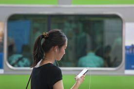 Young Woman with Smartphone at Shinjuku Station in Tokyo, Japan