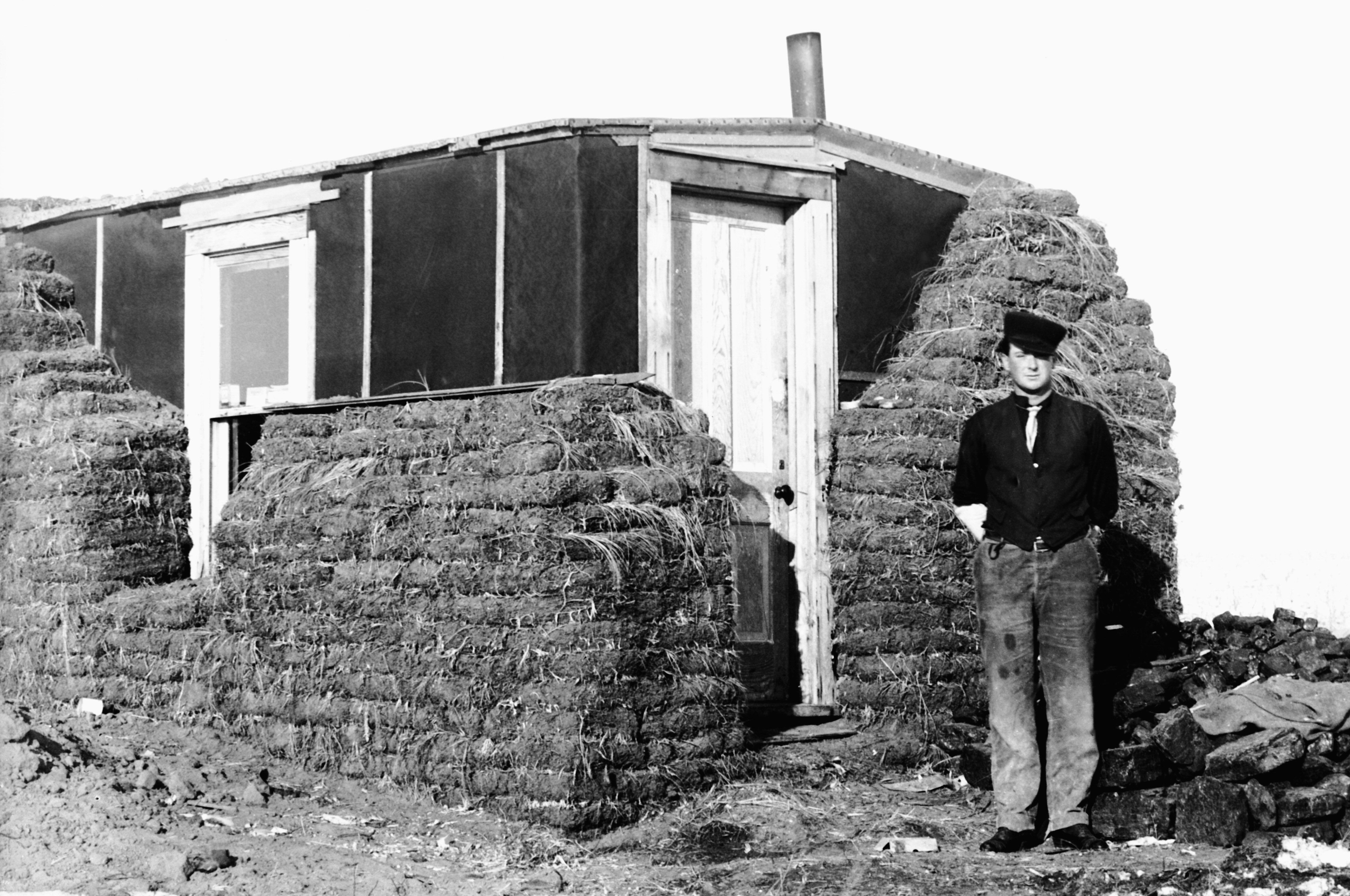 historic black and white photo of man standing near a tar-papered shack being covered by blocks of sod