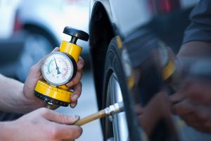 Man checking tire pressure with a gauge