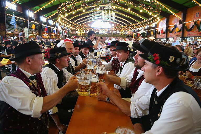 Men in their traditional Bavarian clothing clink beer mugs at Oktoberfest in Munich, Germany