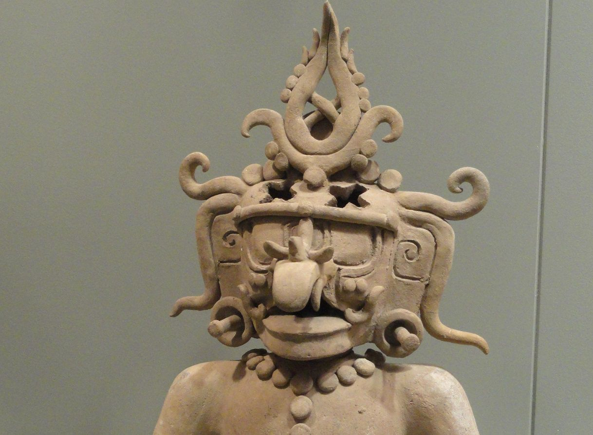 Sculpture of a Mayan god on display at a museum.