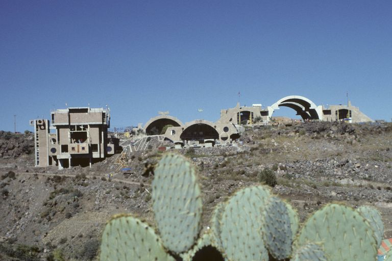 Cactus in foreground, modern experimental buildings dot the desert in the background